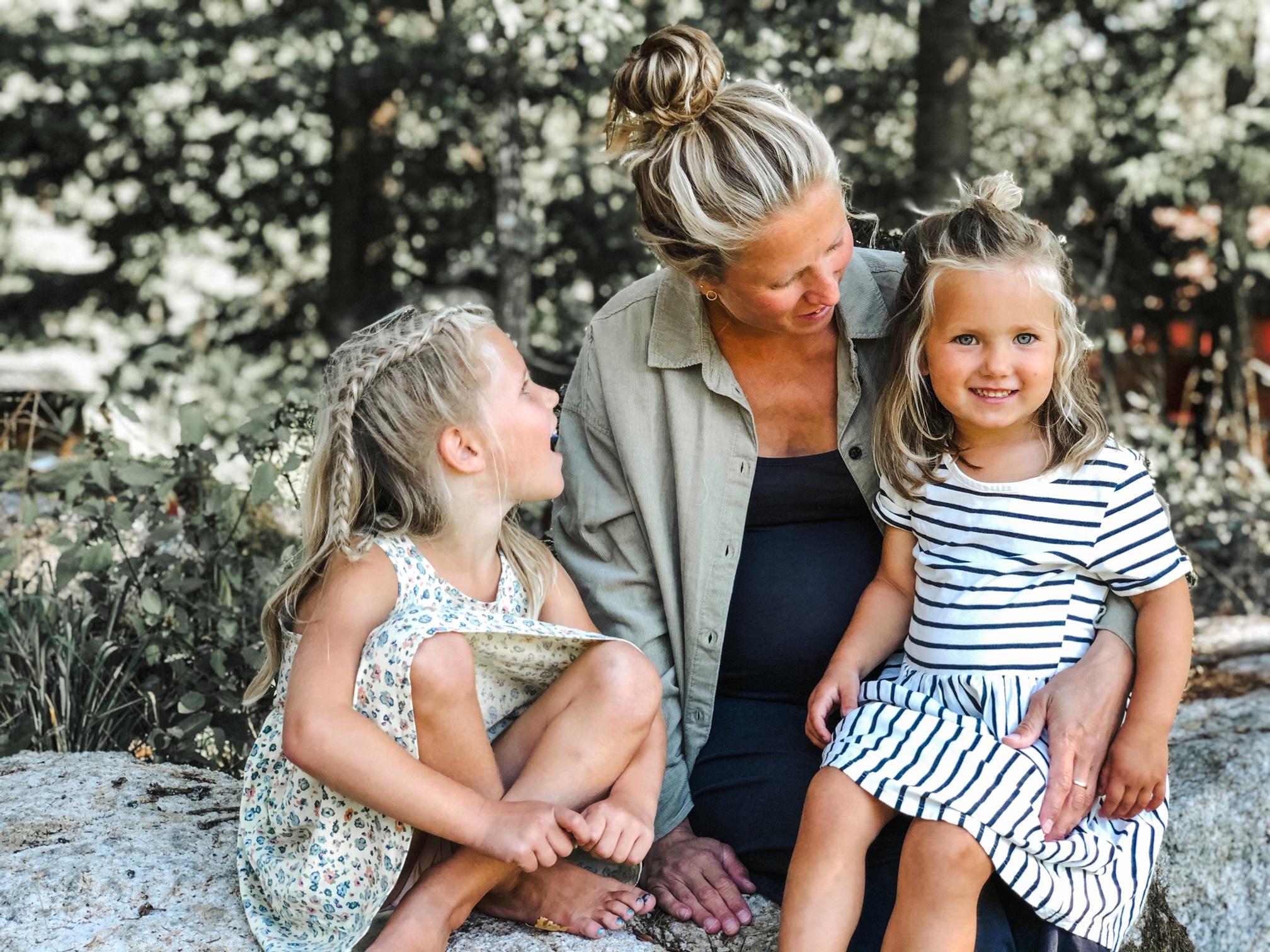 Mor med sine to barn ute i naturen.